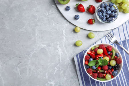 Fresh tasty fruit salad on grey marble table, flat lay. Space for text