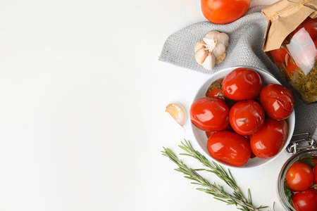 Flat lay composition with pickled tomatoes in glass jars on white table