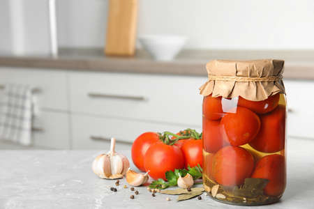 Jar with pickled tomatoes and vegetables on grey table in kitchen. Space for text
