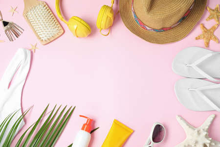 Flat lay composition with beach accessories on pink background, space for text