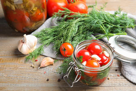 Pickled tomatoes in glass jars and products on wooden table