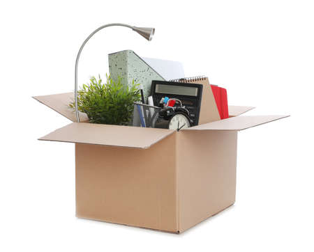 Cardboard box full of office stuff on white background Stock Photo