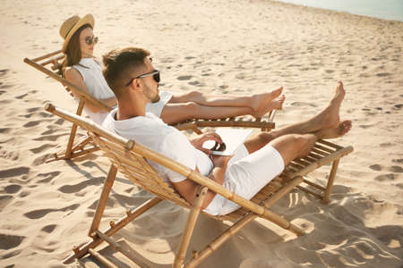 Young couple relaxing in deck chairs on sandy beach 版權商用圖片