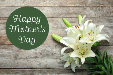 Beautiful lily flowers and text Happy Mothers Day on wooden background, top view