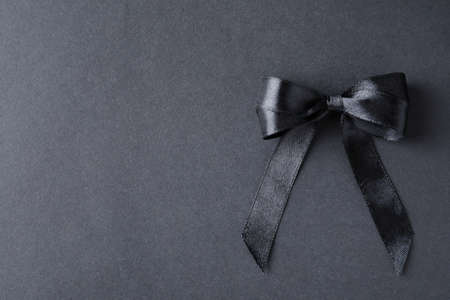 Black ribbon bow on dark background, top view with space for text. Funeral symbol