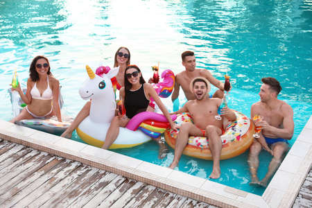 Happy young friends with refreshing cocktails relaxing in swimming pool 版權商用圖片 - 130144470