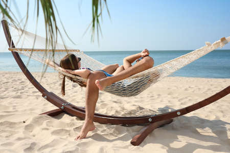 Young lovely relaxing in hammock on beach