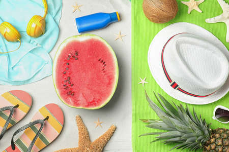 Flat lay composition with watermelon and beach accessories on sand