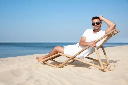 Young man relaxing in deck chair on sandy beach 版權商用圖片