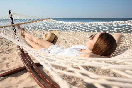 Young woman relaxing in hammock on beach