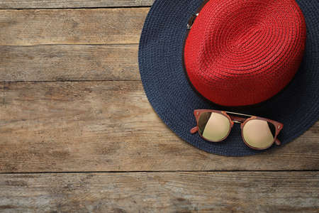 Hat with sunglasses and space for text on wooden background, flat lay. Beach accessories