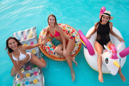 Happy young friends relaxing in swimming pool