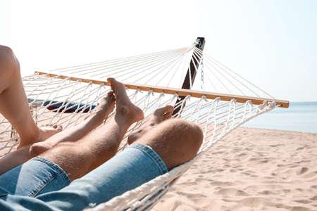 Young couple relaxing in hammock on beach, closeup Reklamní fotografie