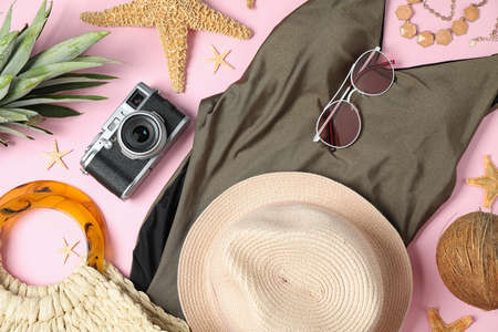 Composition with beach accessories and swimwear on pink background, flat lay
