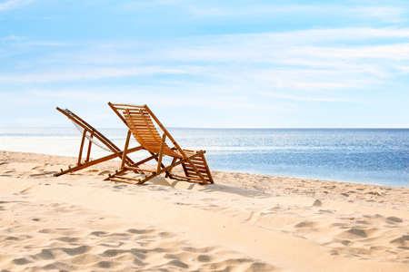 Wooden deck chairs on sandy beach near sea