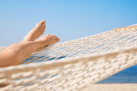 Young woman relaxing in hammock on beach, closeup Zdjęcie Seryjne