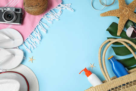 Frame with beach accessories and space for text on light blue background, flat lay Zdjęcie Seryjne