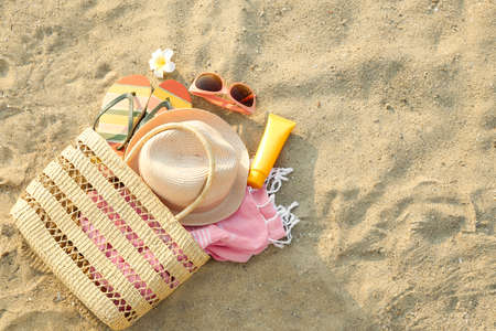 Composition with beach accessories on sand, flat lay. Space for text