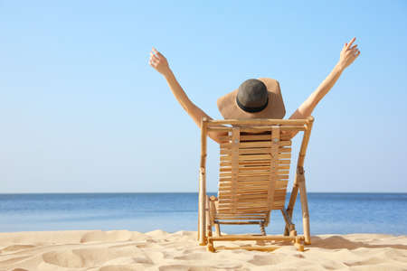 Young woman relaxing in deck chair on sandy beach