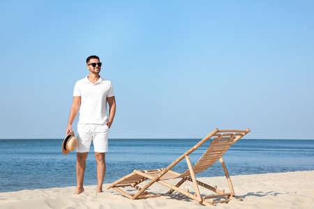 Young man near deck chair on beach near sea