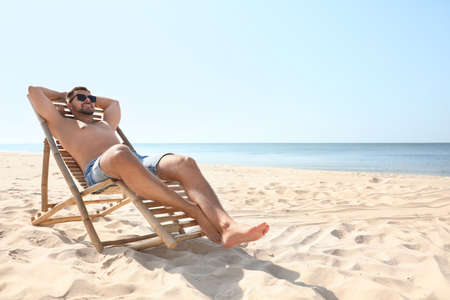 Young man relaxing in deck chair on sandy beach