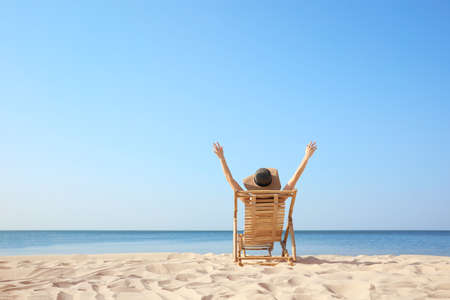 Young woman relaxing in deck chair on sandy beach 版權商用圖片
