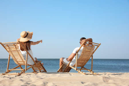 Young couple relaxing in deck chairs on beach