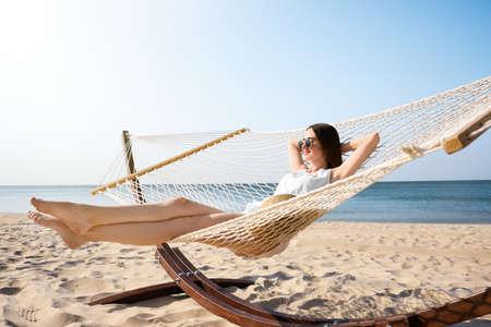 Junge Frau, die sich in der Hängematte am Strand entspannt Standard-Bild