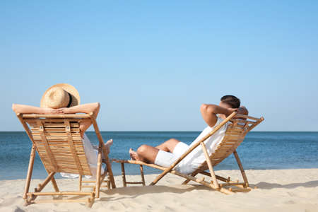 Young couple relaxing in deck chairs on beach Imagens