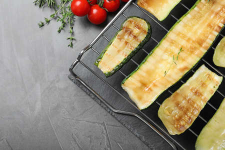Flat lay composition with delicious grilled zucchini slices on grey table. Space for text