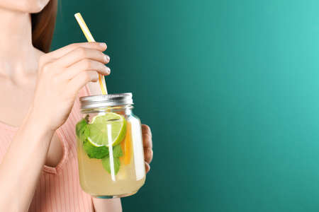 Woman with Mason jar of natural detox lemonade on green background, closeup. Space for text
