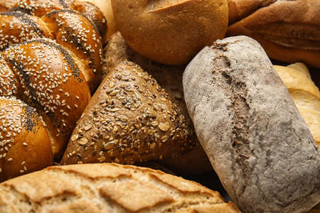 Fresh breads and pastry as background, closeup