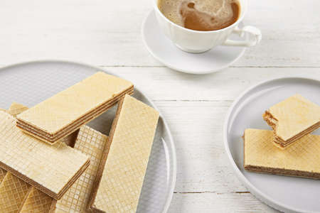 Plates of delicious wafers with cup of coffee  on white wooden background Stok Fotoğraf