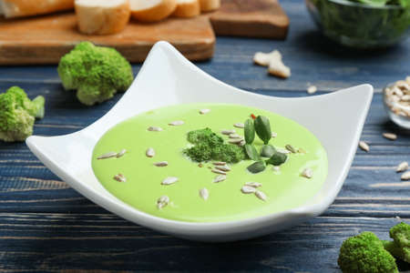 Bowl of cheese cream soup with broccoli and sunflower seeds served on blue wooden table Фото со стока