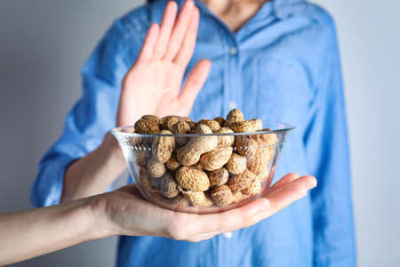 Woman refusing to eat peanuts, closeup. Food allergy concept Stock Photo