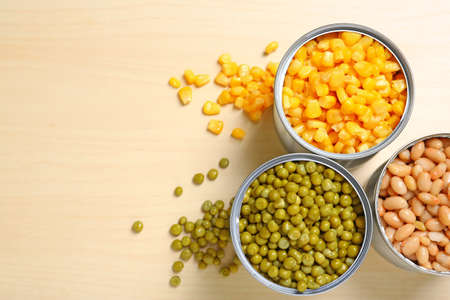 Open tin cans of conserved vegetables on wooden background, flat lay with space for text