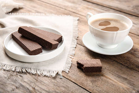 Plate of delicious chocolate wafers with cup of coffee on brown wooden background