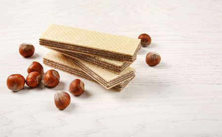 Delicious wafers with hazelnuts on white wooden background
