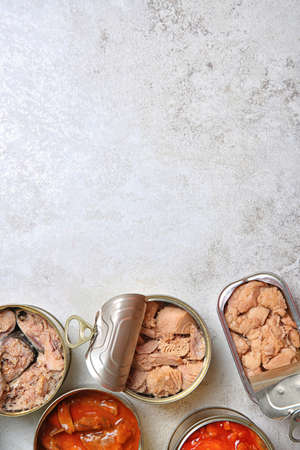 Tin cans with fish on grey table, flat lay. Space for text Stock Photo