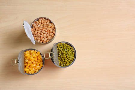 Open tin cans of conserved vegetables on wooden table, flat lay with space for text