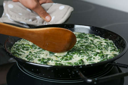 Woman cooking tasty spinach dip on kitchen stove, closeup view
