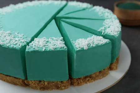 Sliced tasty spirulina cheesecake on dark grey table, closeup view 版權商用圖片