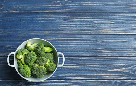 Colander of fresh broccoli on blue wooden table, top view with space for text
