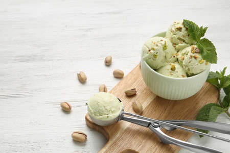 Tasty pistachio ice cream served on white wooden table, space for text