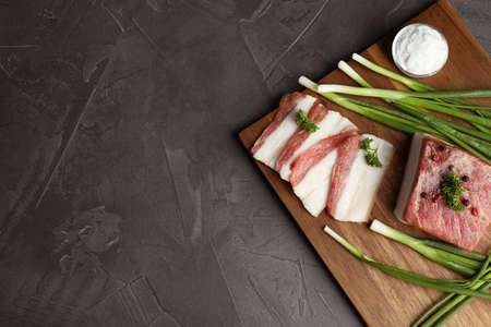 Board with pork fatback, onions and salt on black stone background, top view. Space for text 写真素材