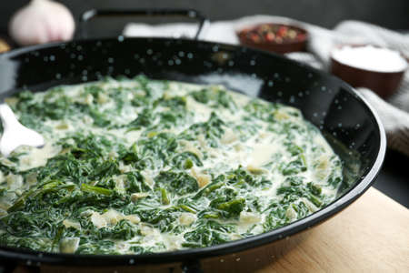 Tasty spinach dip in frying pan on table, closeup