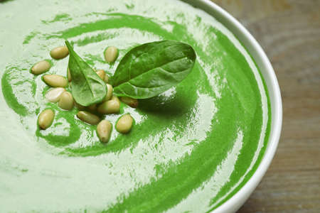 Bowl of healthy green soup with fresh spinach on wooden table, closeup view