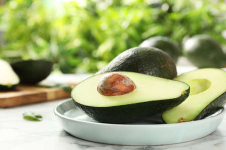 Delicious ripe avocados on table against blurred background