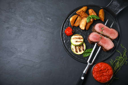 Flat lay composition with slices of grilled meat on black table. Space for text