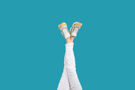 Woman in stylish sport shoes on light blue background Archivio Fotografico - 129903024